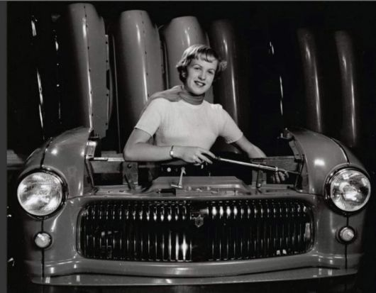 Model standing in the engine bay of the front section of a car.
