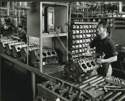 Two men working on the 289 cubic inch V8 engine blocks.