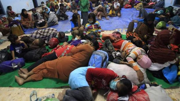 Villagers evacuated from their homes due to Mount Kelud's eruptions, sleep on the floor at a temporary shelter at Sumber ...