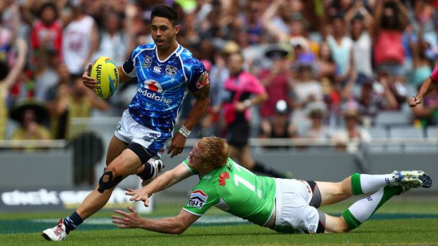 Too classy ... Shaun Johnson of the Warriors beats Joel Edwards of the Raiders to score a try.