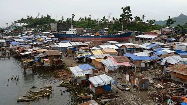 A cargo ship washed ashore at the height of super Typhoon Haiyan, lying amongst makeshift houses along the coastal area ...