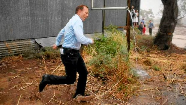 Bringing the rain: Prime Minister Tony Abbott runs for cover during a tour of drought-affected areas that included ...