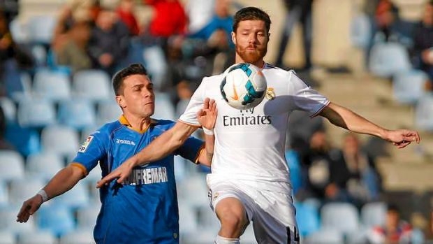 Eye on the ball: Real's Xabi Alonso in action with Getafe's Colunga.