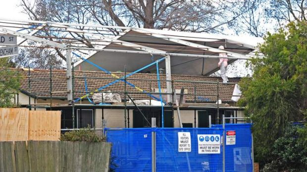 Workers wrap a plastic shield over a house in Downer for the safe removal of asbestos last year.