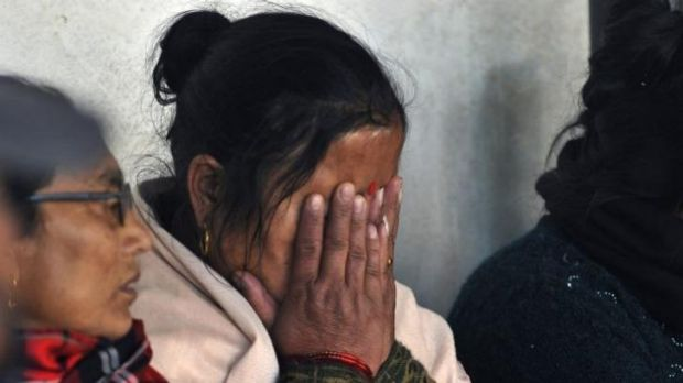 A woman mourns as the victims of a plane crash are taken for a post-mortem at a teaching hospital in Kathmandu.