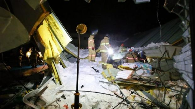Search: Rescue workers look for survivors in the collapsed building.