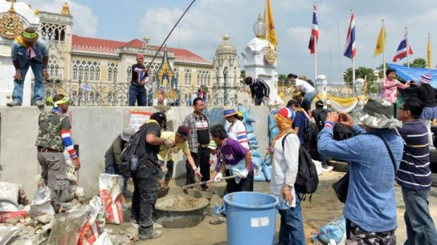 Anti-government protesters mix concrete in an attempt to build a wall in front of the gate of the Government House in ...