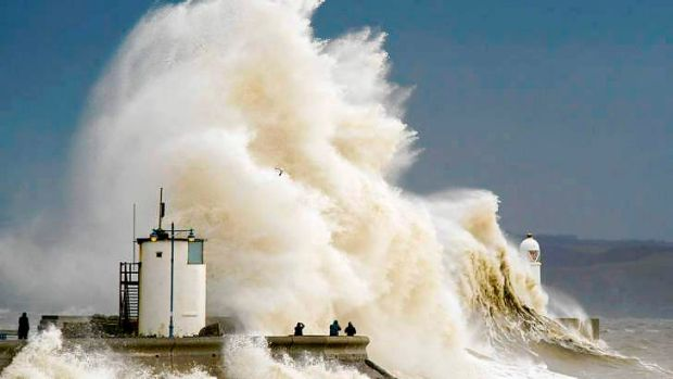 Spectators watch as waves break over the harbour wall at Porthcawl in Wales.