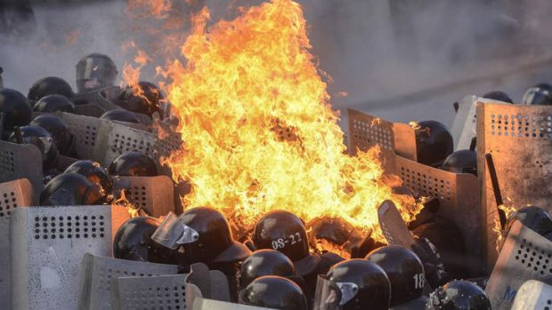 A molotov cocktail hurled by anti-government protesters lands on top of riot police in Kiev.