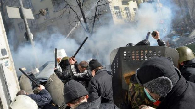 Protesters throw rocks at police in front of the Ukranian Parliament on Tuesday.