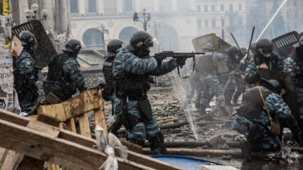 Berkut riot police shoot rubber bullets toward anti-government protesters on Kiev's Independence Square.