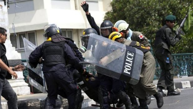 Police carry an injured colleague after a grenade was thrown into their ranks by anti-government protesters in Bangkok.