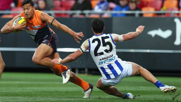 Playing against the Kangaroos: Folau evades a North Melbourne opponent while playing for GWS Giants in 2012.