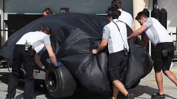 Kevin Magnussen's Formula One car is pushed into the McLaren garage.