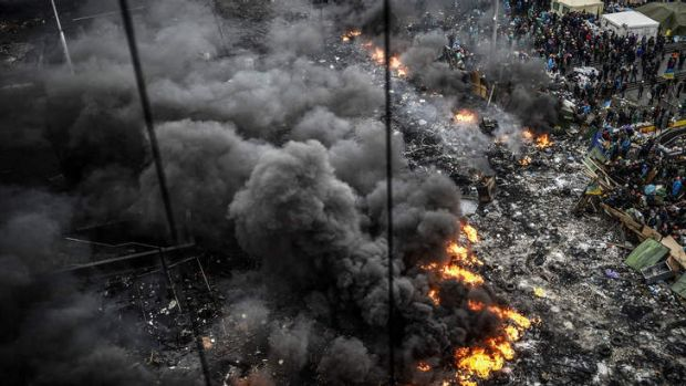 Protesters stand behind burning barricades during the confrontation with police in Independence Square, known in ...