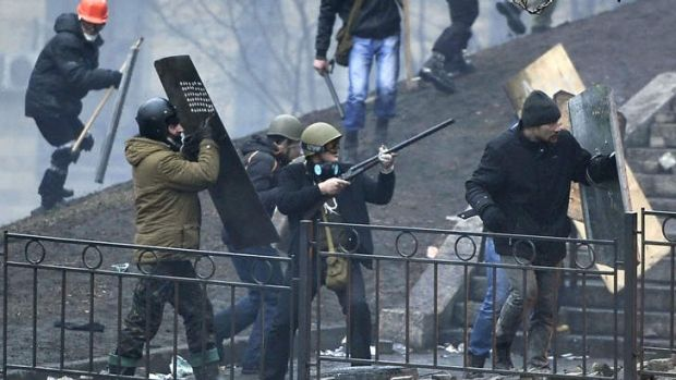 A protester aims a rifle towards riot police as protesters advance near Independence Square.