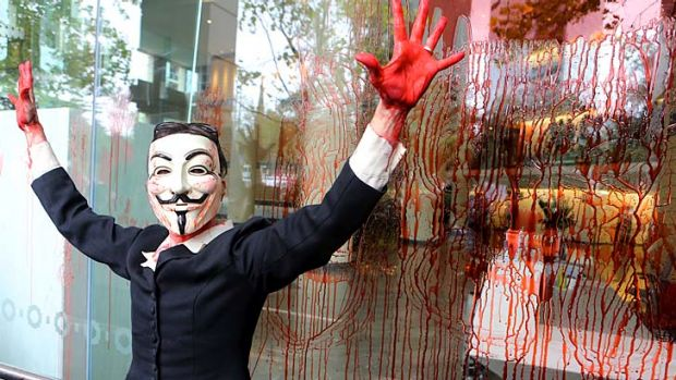A protester smears fake blood on the immigration office in Lonsdale Street while a crowd chants that the government has ...