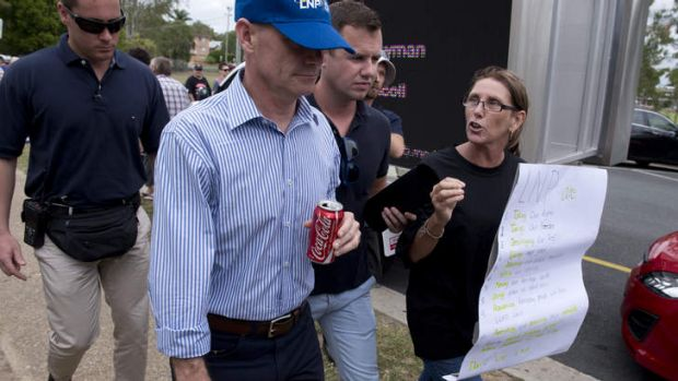 Premier Campbell Newman is yelled at by a protester after leaving the Humpybong state school in Redcliffe where he was ...
