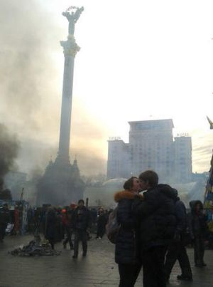 A young couple embrace as smoke rises above Independence Square.