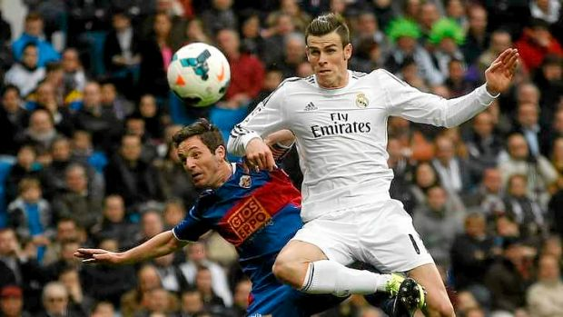 Flying high: Real Madrid's Gareth Bale challenges Elche's Edu Albacar for the ball.