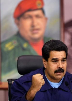 Defiant: Venezuelan President Nicolas Maduro speaks to the media in front of a portrait of his dead predecessor, Hugo Chavez.
