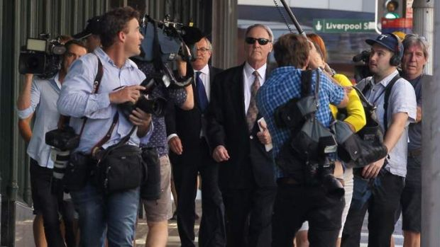 A media scrum surrounds Robert Hughes as he leaves the Downing Centre.