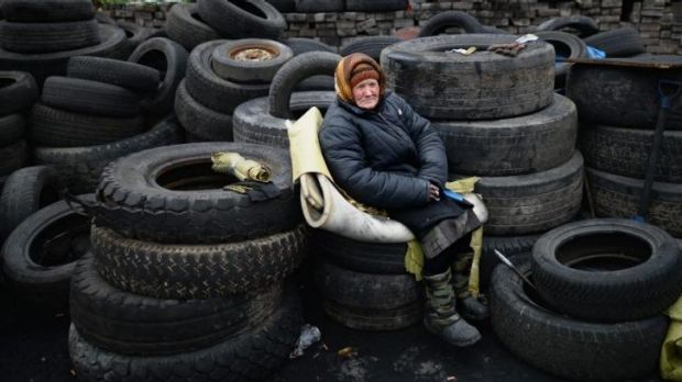 An elderly woman sits on tyres at a barricade in independence square.