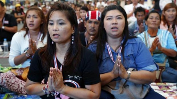 Anti-government protesters pray near the site of a bomb blast in Bangkok that killed two people and wounded at least 22.
