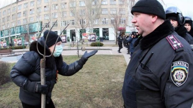 A supporter of ousted president Viktor Yanukovych tries to reach anti-government protesters celebrating victory in the ...