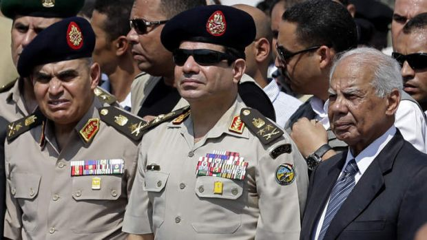 Egyptian Defence Minister General Abdel-Fattah el-Sisi, centre, and interim Prime Minister Hazem el-Beblawi, right in 2013.