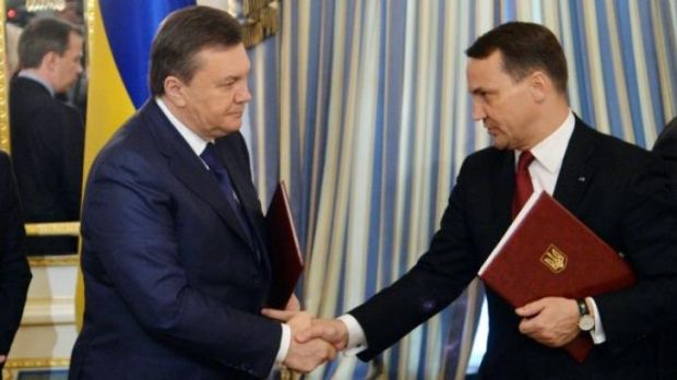 Former Ukrainian president Viktor Yanukovych (L) and Polish Foreign Affairs Minister Radoslaw Sikorski shake hands on a ...