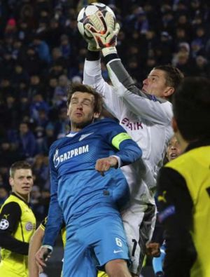 Zenit St Petersburg's Nicolas Lombaerts (L) fights for the ball with Borussia Dortmund's goalkeeper Roman Weidenfeller.