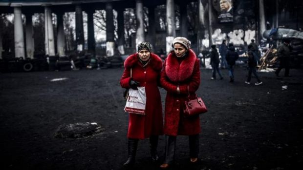 Women walk in front of a football stadium in KIev.