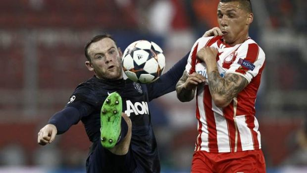 Wayne Rooney fights for the ball with Olympiakos' Jose Holebas.