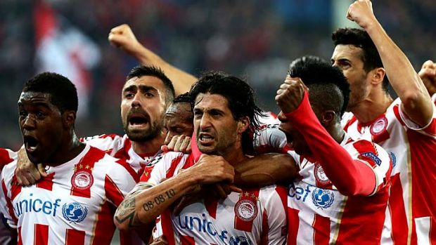 Olympiakos' midfielder Alejandro Dominguez (centre) celebrates with teammates after scoring a goal during the match ...