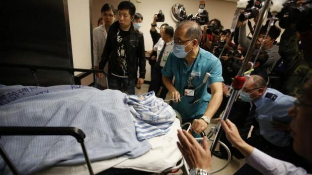 Critical condition ... former Ming Pao chief editor Kevin Lau Chun-to is wheeled into the operation theatre at a ...