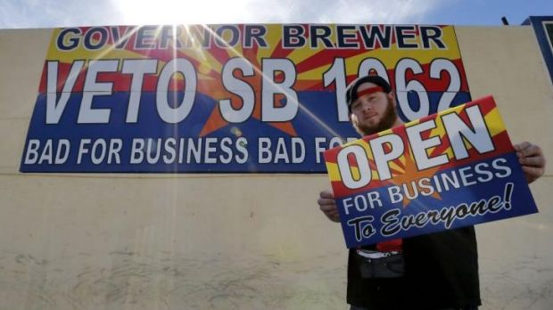 "A protester against Senate Bill 1062 shows a sign that reads ""Open For Business To Everyone"" in Phoenix, Arizona."