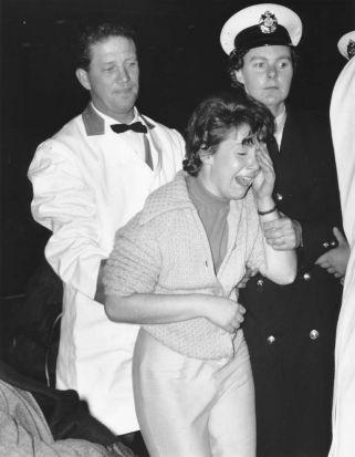 A teenage fan overcome by her emotions is escorted from the Beatles concert at Festival Hall by an usher and policeman, ...
