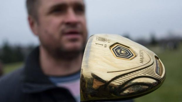 Missing his driver ... a man holds a golf club bearing the name of ousted Ukrainian President Viktor Yanukovich.