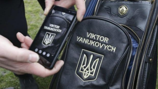 Swinging freely ... A man takes a photo of ousted Ukraine president Viktor Yanukovich's personalised golf bag.