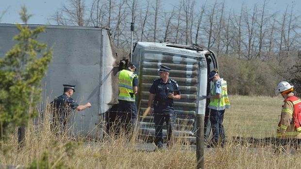 Police examine the truck at the crash site.