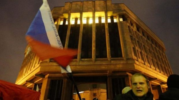 A man waves a Russian flag in front of a local parliament building during a pro-Russian rally in Simferopol, Crimea.