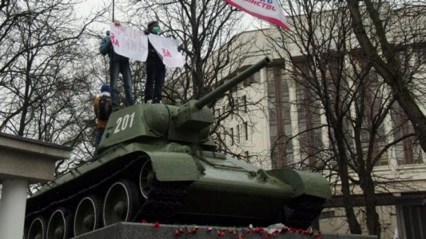 Pro-Russian demonstrators stand on a T-34 Soviet tank, set as a WWII monument in the Crimean parliament in Simferopol.