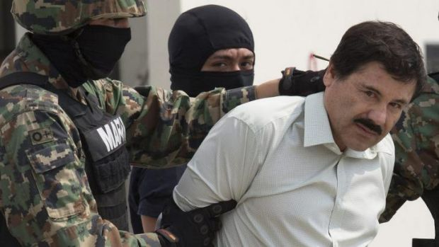 "Finally captured ... drug trafficker Joaquin ""El Chapo"" Guzman is escorted to a helicopter by Mexican security forces at ..."