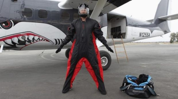 Daredevil jumper Joby Ogwyn shows reporters his prototype wing-suit.