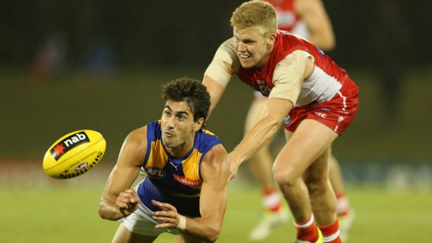 West Coast's Matt Rosa gets a handball away despite pressure from Ryan O'Keefe, during the Eagles'  35-point victory ...