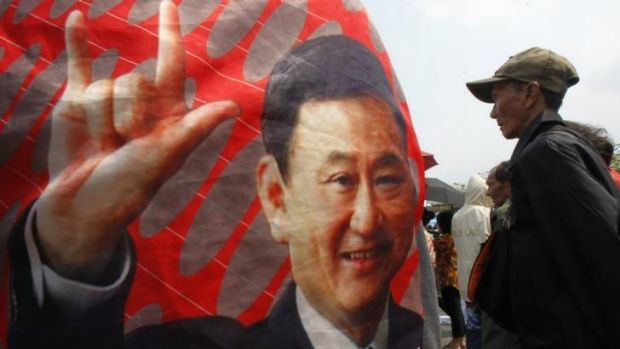Divisive: A government supporter stands next to a picture of former Thai Prime Minister Thaksin Shinawatra.