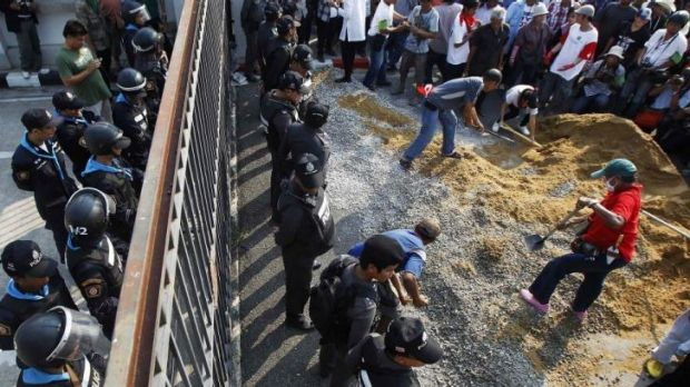 Government supporters begin to build a wall at the gates of the National Anti-Corruption Commission, where prime ...