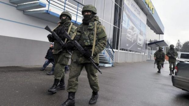 Unidentified armed men patrol outside of the Simferopol airport. Ukraine's interim government has accused Russia of ...