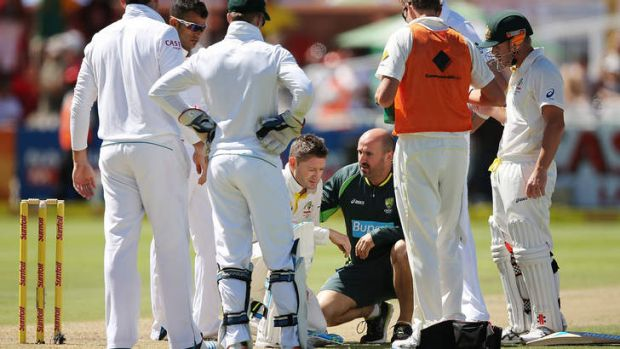Michael Clarke receives treatment after getting hit by a delivery from Protezs paceman Morne Morkel.